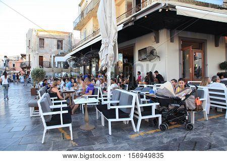 CRETE, GREECE - JULY 21, 2016: People sit in sidewalk street cafe in Rethymno waterfront on Crete island, Greece