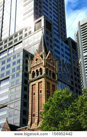 Bell tower of St-Michael uniting church with business buildings in background in Melbourne, Australia