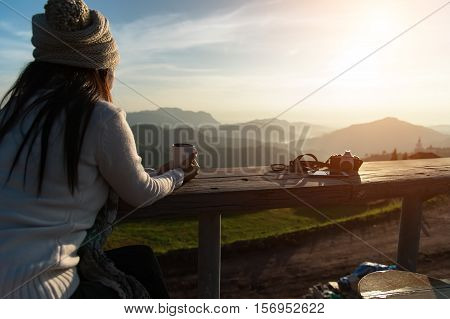 Woman drinking coffee in sun sitting outdoor in sunshine light enjoying her morning coffee vintage soft and select focus