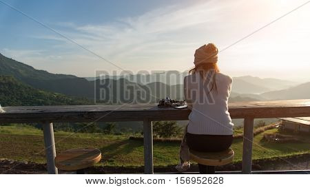 Woman drinking coffee in sunshine sitting outdoor in sun light enjoying her morning coffee. Smiling happy multiracial female Asian Chinese