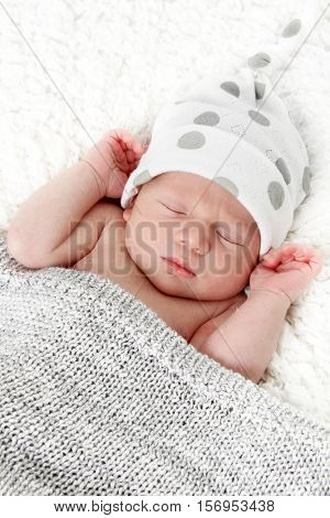 Newborn baby boy asleep on a blanket.