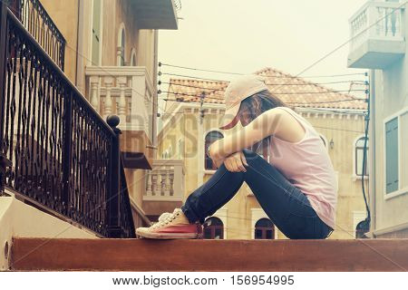 sad woman wearing a cap and hugging knees on stair she is lonely most of the time vintage tone