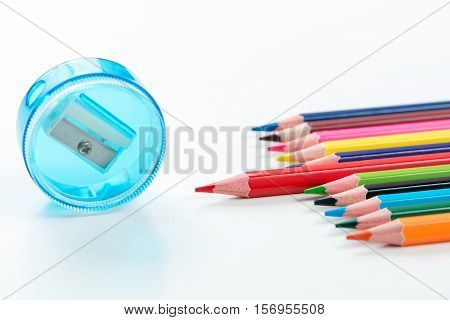 Sharpener and colorful crayons in white background