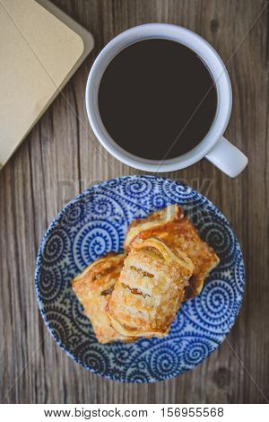 Fresh puff pastries and coffee cup with blank book on wooden background