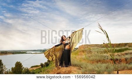 Oriental Beauty dance with wings. Nice girl in national dress dancing in the open air. Nomads.