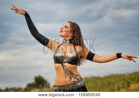 Oriental Beauty belly dancer. Nice girl in national dress dancing in the open air. Nomads.