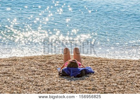 Sunbathing by the sea on the Tucepi town beach.