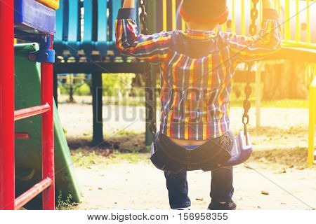 Little boy swinging in playground of japan.Or child playing in the playground and sunshine view.
