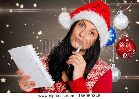 Portrait of thoughtful woman in santa hat holding pen and diary during christmas time