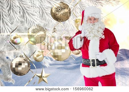Portrait of santa claus holding his gift sack against digitally generated christmas background