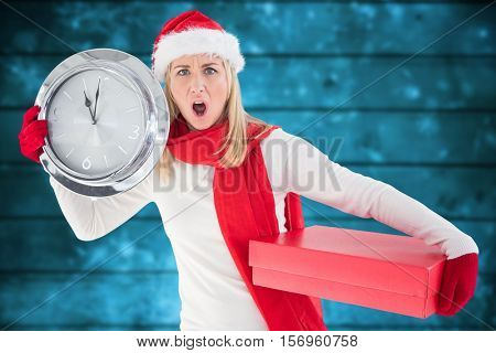 Portrait of anxious woman in santa hat holding a clock and christmas gift