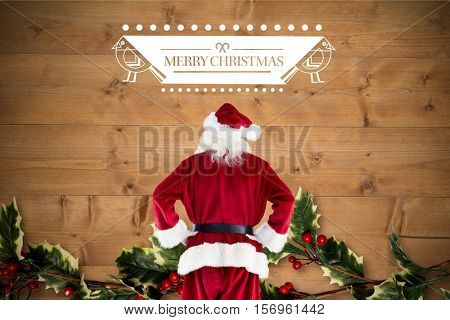 Santa claus standing with hands on hips against digitally generated background during christmas time