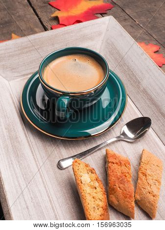 Italian cantuccini with a cup of espresso on a wooden plate