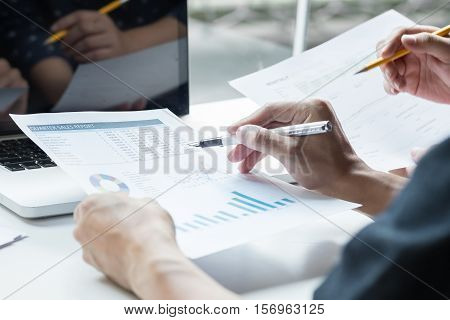 Two business partners analysing a financial report discussing the statistics and performance of their company.