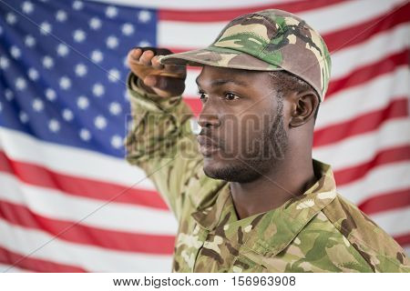 Close- up of soldier saluting against american flag