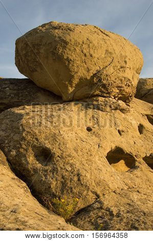 A golden sandstone formation with crevices and holes viewed at an angle at sunset at Zimmerman Park, Billings Montana