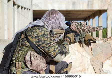 Sniper aim target scope ghillie suit camouflage lying on the floor cover wall