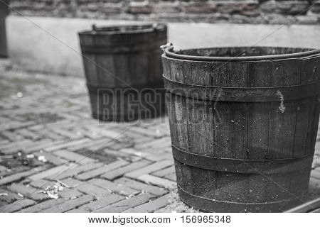 two old wooden buckets. standing on the pavement