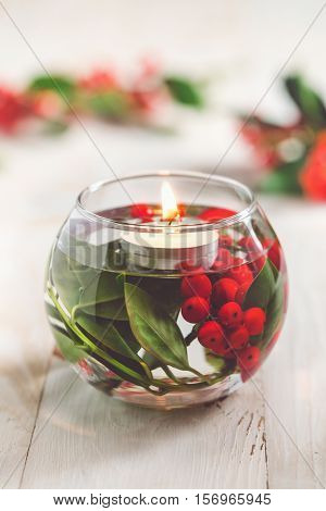 Christmas Table Decoration. Glass vase with holly berries and white floating candle.