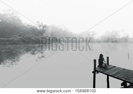 Young women sitting on a wooden bridge. Black and white picture