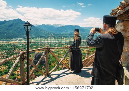 Trikala Meteora Greece - May 25 2015: The priest takes a picture of another priest on the lookout of The Holy Monastery of Great Meteoron against the Thessalian valley, Meteora, Trikala, Greece