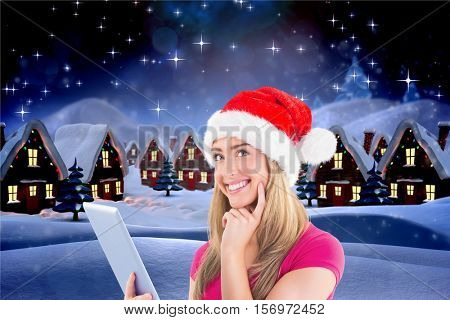 Beautiful woman in santa hat using digital tablet against digitally generated background