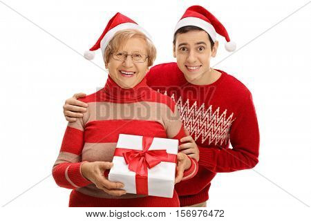 Elderly woman and a young man wearing Santa hats posing with a Christmas present isolated on white background