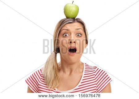 Horrified young woman with an apple on her head isolated on white background