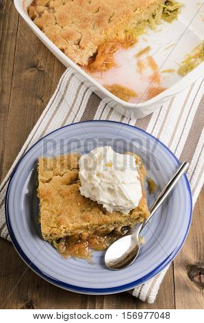 rhubarb crumble cake with whipped cream and spoon on a blue plate