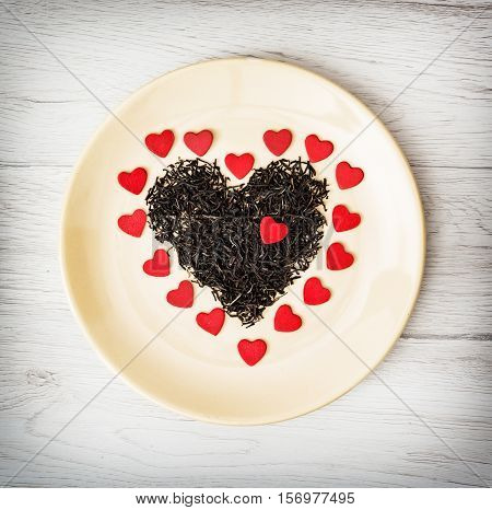Heart of black loose tea from Ceylon and little red paper hearts on the plate. Valentine's day. Symbol of lovers.