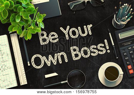 Be Your Own Boss Handwritten on Black Chalkboard. Top View of Black Office Desk with a Lot of Business and Office Supplies on It. 3d Rendering. Toned Image.