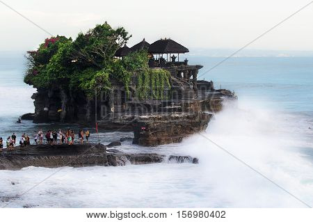 Bali Indonesia - April 4 2016: Tanah Lot is a rock formation off the Indonesian island of Bali. It is home to the pilgrimage temple Pura Tanah Lot a popular tourist and cultural icon for photography and general exoticism.