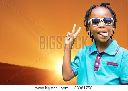 Child making wince against scenic view of landscape against orange sky