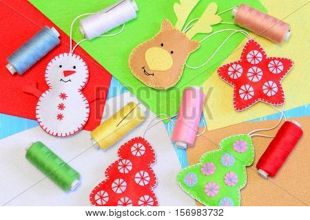 Felt Christmas ornaments. Colorful stuffed felt snowman, reindeer, Christmas tree, flat felt sheets, colored thread, needle. Fun Christmas crafts background. Holiday handmade idea for children
