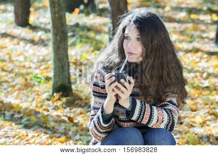 Young woman in knitted snowflakes pattern woolen sweater is drinking hot yerba mate