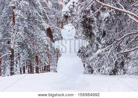 Snowman with broom in the glade on the background of snow-covered pine forest