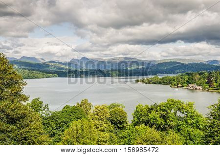 View of Lake Windermere from the south surrounded by trees and distant mountains under a mostly gray sky.