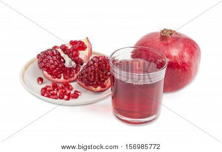 Pomegranate juice in a glass one whole pomegranate and peeled pomegranate on a saucer on a light background
