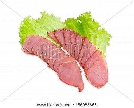 Sliced cured pork tenderloin on a lettuce leaves on a light background