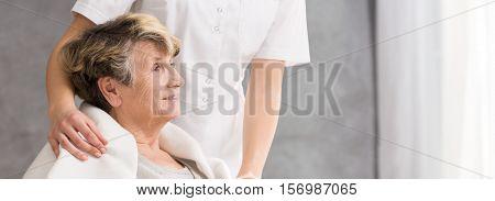 Nurse Standing Behind Senior Woman