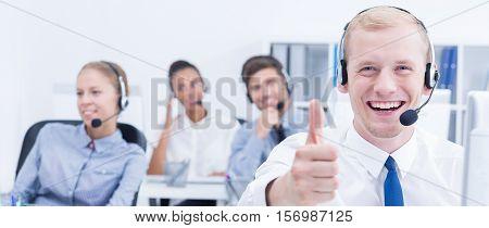 Satisfied smiling telemarketing team operating at work
