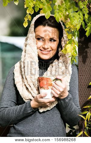 Beautiful green eyed young woman in warm clothes and beige scarf smiling, holding a cup of tea outdoors, in autumn time