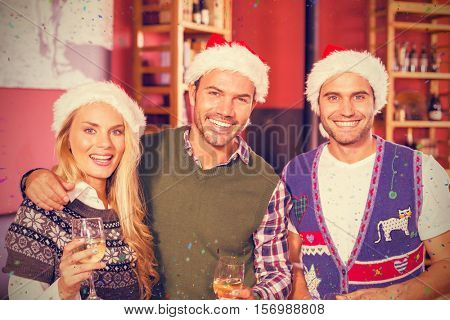 Portrait of friends wearing Christmas hats against flying colours