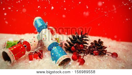 Snow falling against christmas crackers and decoration on snow