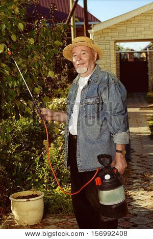 Senior man pollinate trees in the garden with pests spray. Gardening and vegetable farming.