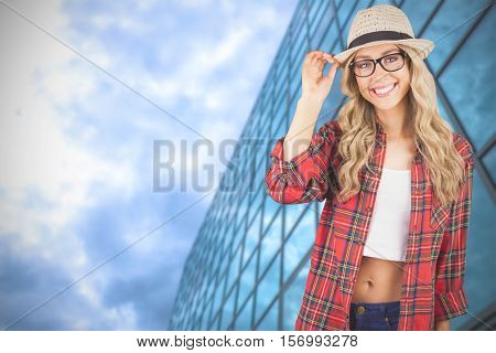 Gorgeous smiling blonde hipster posing against low angle view of glasses skyscraper