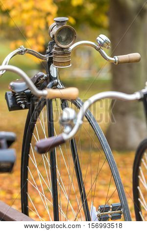 A penny-farthing bicycle with an old headlamp in a park with fallen autumn leaves