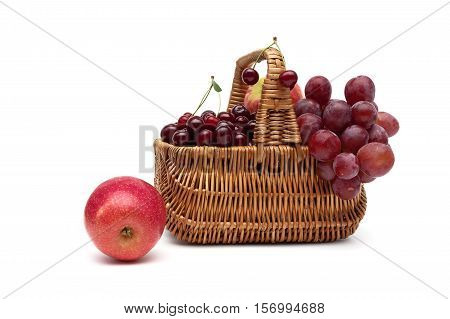 fresh fruit in a wicker basket on a white background. horizontal photo.