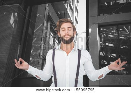 Hipster meditating arms outstretched against exterior of modern building