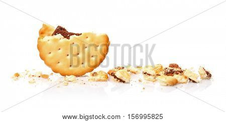 Tasty cookie and crumbs on white background